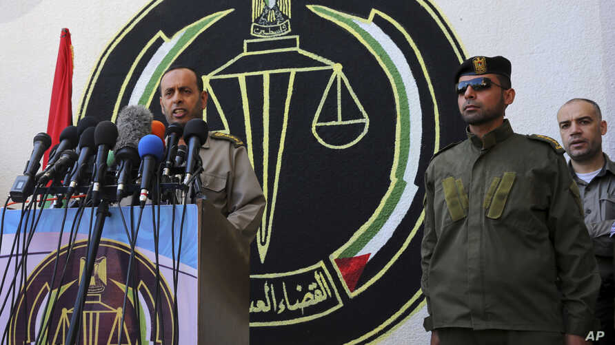 FILE - Nasser Suliman, head of military judiciary, announces during a press conference that the military court sentenced to death three men convicted of killing Mazen Faqha, a top militant commander in March, at Hamas military judiciary building in G