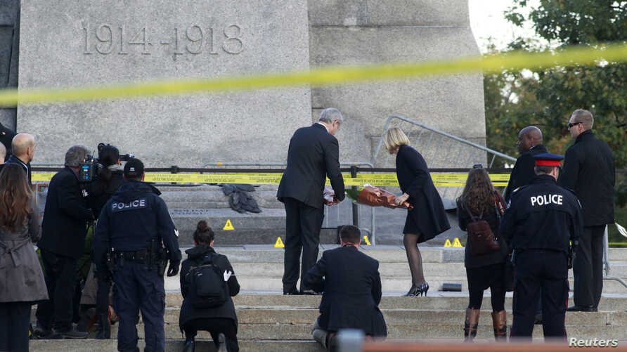 Canada's Prime Minister Stephen Harper and his wife, Laureen Harper, lay flowers at the Canadian War Memorial in downtown Ottawa October 23, 2014.