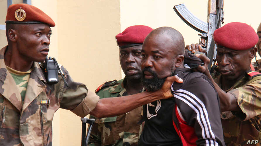 FILE - Members of the armed forces arrest Central African Republic MP Alfred Yekatom after he fired the gun at the parliament in Bangui, Oct. 29, 2018. Yekatom was extradited Nov. 17, 2018, to The Hague, The Netherlands, after an arrest warrant was i...