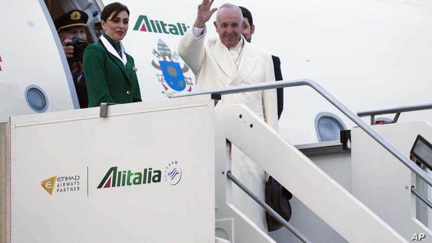 Pope Francis waves as he boards an airplane at Rome's Fiumicino airport on his way to a week-long trip to Mexico, Friday, Feb. 12, 2016.