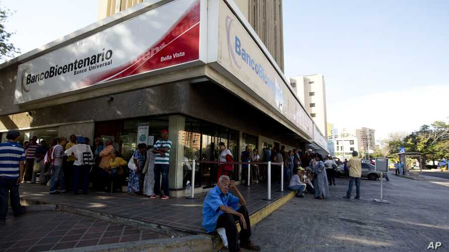 Customers wait outside of a government bank to get new bank notes in Maracaibo, Venezuela, Aug. 21, 2018. The new currency has five fewer zeros in a bid to tame soaring inflation.