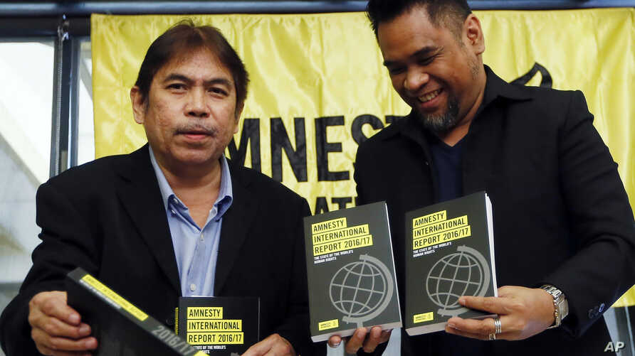 Amnesty International, Philippines' Jose Noel Olano, left, and Wilnor Papa, hold copies of the 2016/17 Amnesty International report which they released at a news conference, Feb. 22, 2017, in suburban Quezon city northeast of Manila, Philippines.