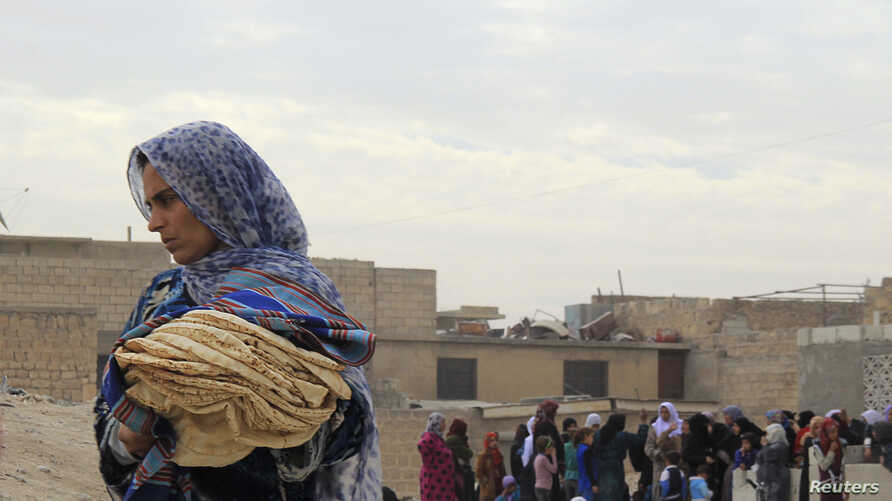 A woman holds bread in Minbij city in the east countryside of Aleppo, Syria, Oct. 18, 2013.