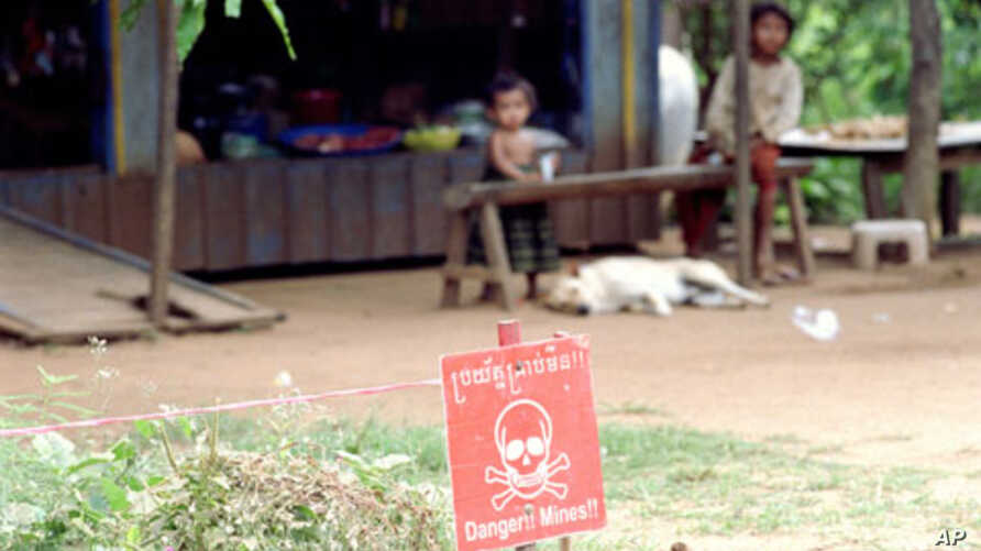 Children sit near a minefield outside their home in the northwestern Cambodian province of Battambang, one of the most heavily-mined in the country