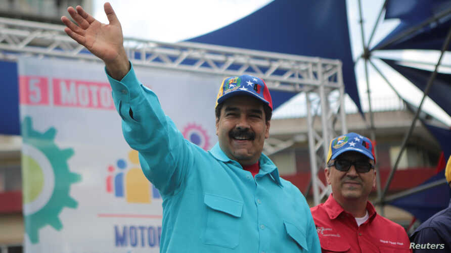 Venezuela's President Nicolas Maduro, left, and Venezuela's Economy and Productivity Vice President Miguel Perez Abad greet supporters during a rally in Caracas, Venezuela, May 14, 2016.