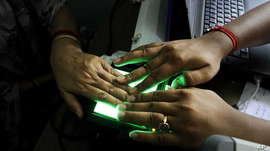 FILE- An operator helps an elderly woman scan her fingerprints as she enrolls for Aadhar, India's unique identification project in Kolkata, India, May 16, 2012. India's top court has ruled that the right to privacy is a fundamental right of every cit