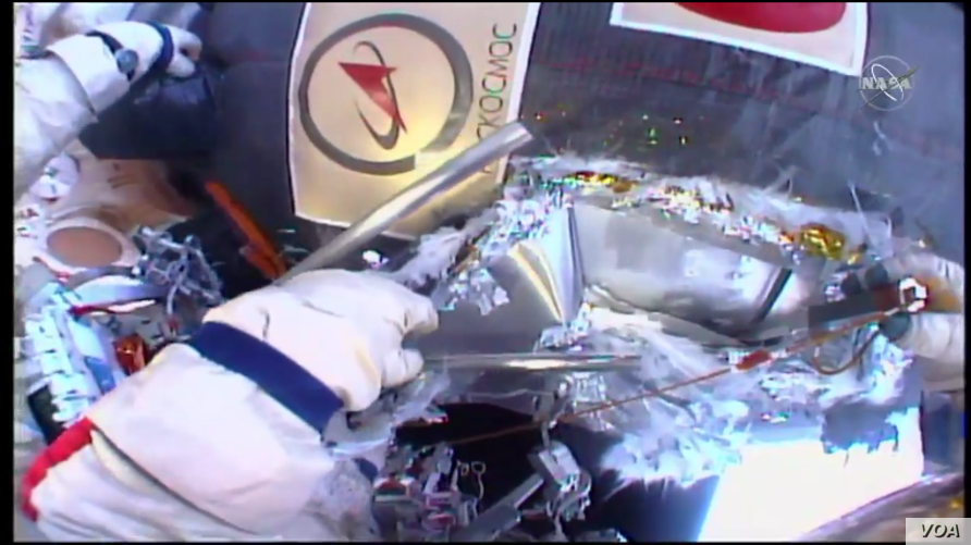 Russian cosmonauts perform a spacewalk, Tuesday, seeking to resolve the mystery of a small hole found in the side of a craft docked at the International Space Station, Dec. 11, 2018. (NASA TV)