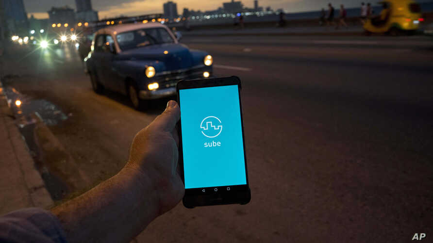 """A man holds his phone showing the app """"Sube,"""" a ride-hailing app for the aging American sedans on the streets of Havana, in Havana, Cuba, Feb. 21, 2019."""
