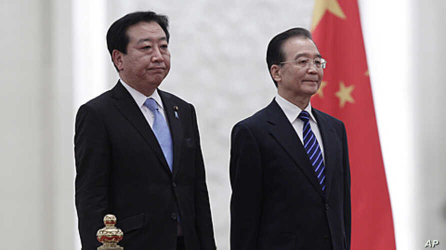 Japan's Prime Minister Yoshihiko Noda (L) and China's Premier Wen Jiabao listen to their national anthems during a welcome ceremony at the Great Hall of the People in Beijing, December 25, 2011