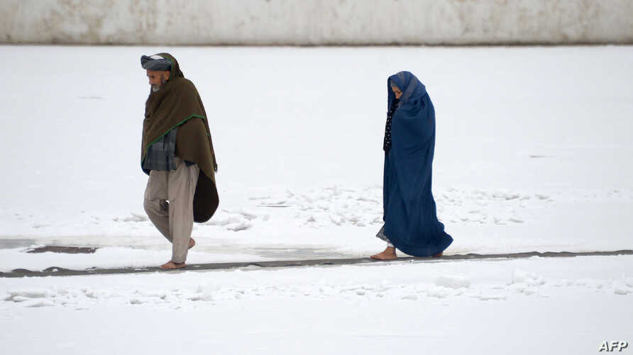 An Afghan couple walk through the snow in the courtyard of the the famous Blue Mosque in Mazar-i-sharif, Nov 24, 2016.