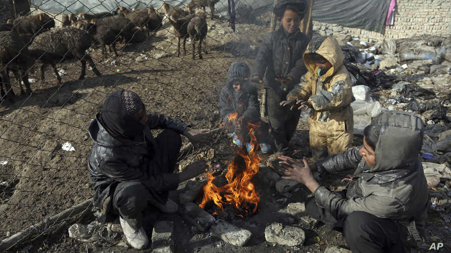 FILE - Afghan boys warm themselves near a bonfire on the cold day in a poor neighborhood on the outskirts of Kabul, Afghanistan, Dec. 17, 2017.