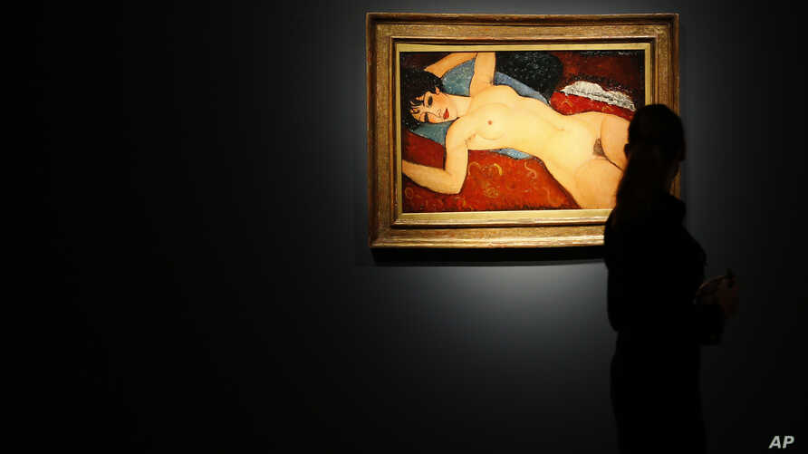 FILE - A member of staff at Christie's auction house looks at a painting by Italian artist Amedeo Modigliani entitled 'Ne Couche' 1917-1918 as it goes on show in London. The painting sold for $170.4 million in New York.