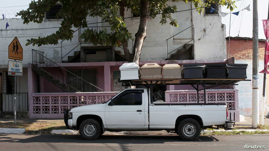 A pick-up truck transports unfinished coffins to another workshop in Jucuapa, El Salvador, April 7, 2016.