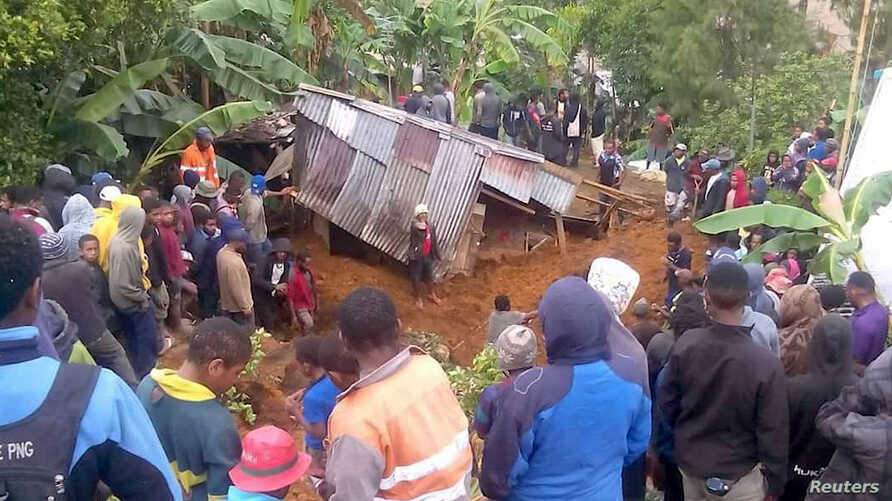 Locals surround a house that was covered by a landslide in the town of Mendi after an earthquake struck Papua New Guinea's Southern Highlands in this image taken Feb. 27, 2018, obtained from social media.