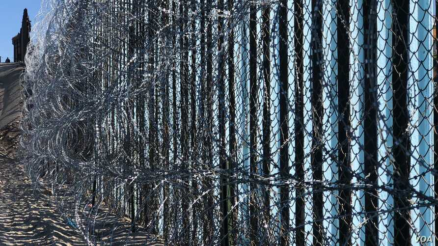 Border wall reinforced with barbed wire to prevent migrants from illegally entering into the United States.