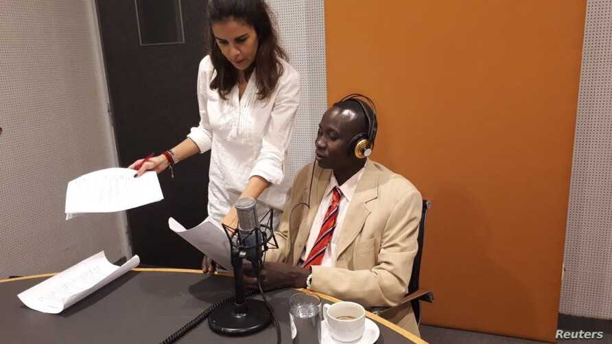 """Abdallah Afandi (R), a Sudanese migrant, tapes an episode for """"Msh gharib"""" radio show meaning """"not foreign"""" in Arabic, with the help of journalist Christine Habib (L) in Beirut, Lebanon, Nov. 9, 2017."""