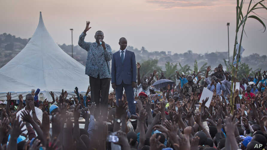 Opposition leader Kizza Besigye, center-left, gestures as he speaks to thousands of his supporters at an election rally at dusk on the outskirts of Kampala, Uganda Sunday, Feb. 14, 2016.