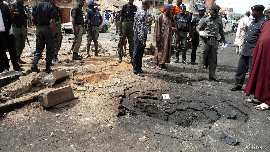 Security officials assess the scene of a bomb blast that killed four people by suspected members of Nigerian Islamist sect Boko Haram in Nigeria's northern city of Kaduna, April 8, 2012. It comes a day after at least 36 people were killed by a car bo