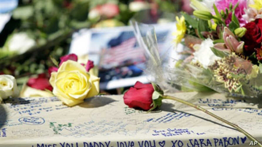 Family members of the victims of 9/11 write notes and leave flowers while they gather around the Ground Zero reflecting pool at the site where the twin towers once stood on the ninth anniversary of the terrorist attacks on the World Trade Center, in