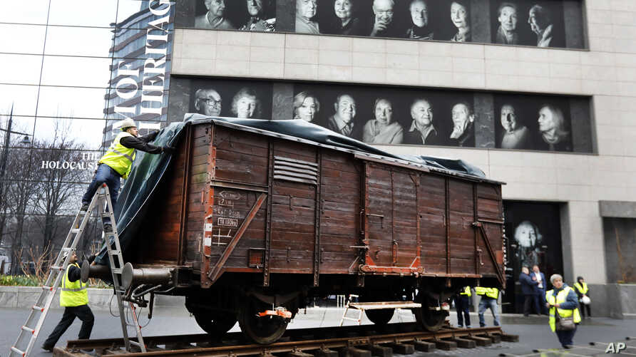 Portraits of Holocaust survivors are displayed at the Museum of Jewish Heritage as a vintage German train car, like those used to transport people to Auschwitz and other death camps, is uncovered on tracks outside the museum, in New York, Sunday, Mar