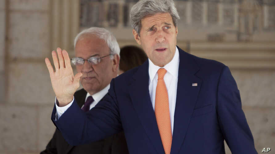 U.S. Secretary of State John Kerry, right, and chief Palestinian negotiator Saeb Erekat arrive at a meeting with Palestinian President Mahmoud Abbas in the West Bank city of Ramallah, July 23, 2014.
