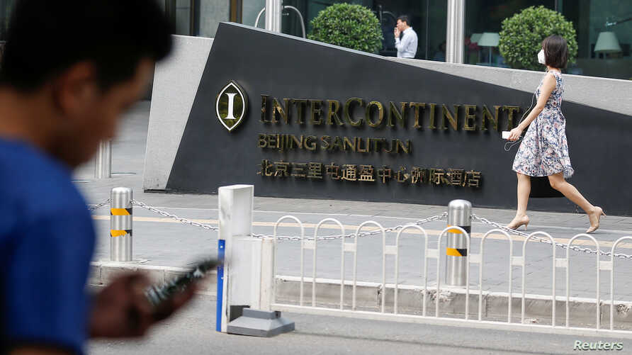 A man uses a phone outside the InterContinental hotel in Beijing district of Sanlitun, China, Aug. 1, 2017. China is filling the holes in it's Great Firewall, and that includes one of the last places to find unfiltered internet content: international