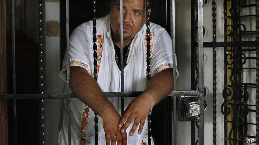 In this July 2, 2016 photo, Juan Carlos Soni Bulos stands behind the wrought iron door of his house in Tanquian de Escobedo, San Luis Potosi, Mexico. Soni was enrolled in a government protection program as of June 26, 2013, but was detained by marine