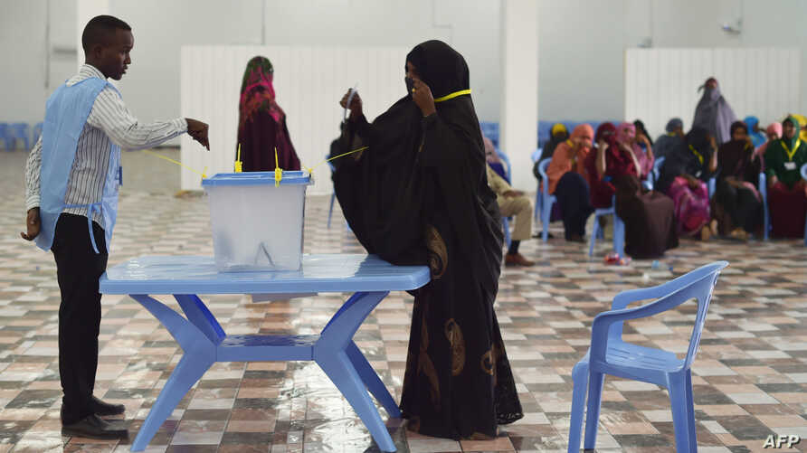 A woman casts her vote during Somalia's parliament election, at a polling station in Mogadishu, Somalia, Dec. 6, 2016. An electoral body on Wednesday annulled the results in 11 races of the poll, citing irregularities.