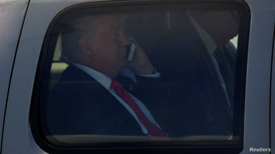 FILE - President-elect Donald Trump, at the time still the Republican presidential nominee, talks on his phone as he is driven to his at a campaign rally in Scranton, Pennsylvania, July 27, 2016.