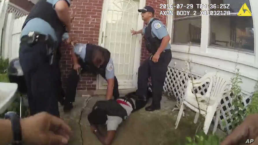 In this frame grab from a body cam provided by the Independent Police Review Authority, Chicago police officers handcuff Paul O'Neal, suspected of stealing a car, after they fired into the vehicle he was driving and then pursued him through a yard.