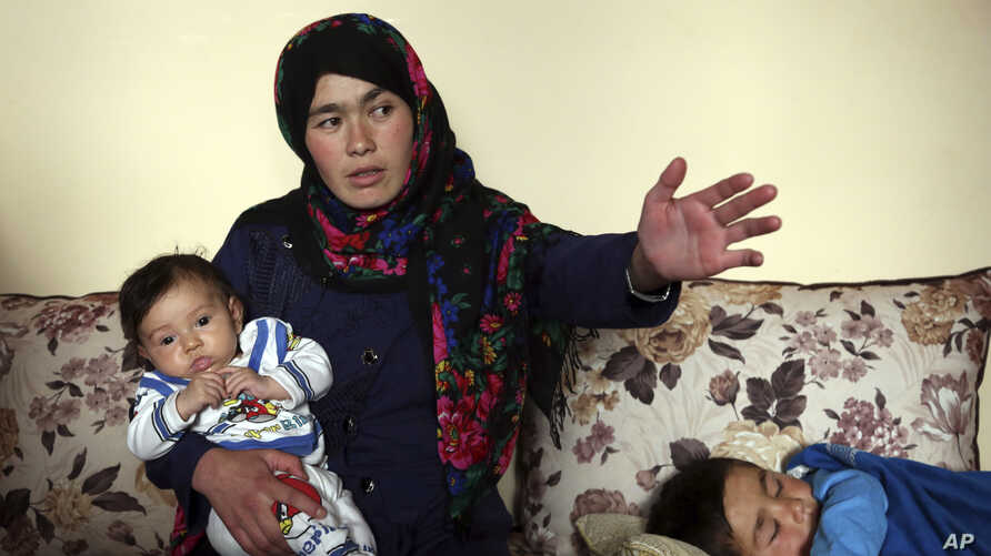 Jahantab Ahmadi, 25, holding her three month-old daughter Khezran, speaks during an interview with the Associated Press in Kabul, March 26, 2018.
