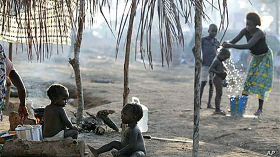 Children sit outside their family's tent as a neighbor bathes her son in a camp housing more than 2,600 Ivorian refugees, with more arriving daily, in Solo Town, near Zwedrou, Liberia, May 2011. (file photo)