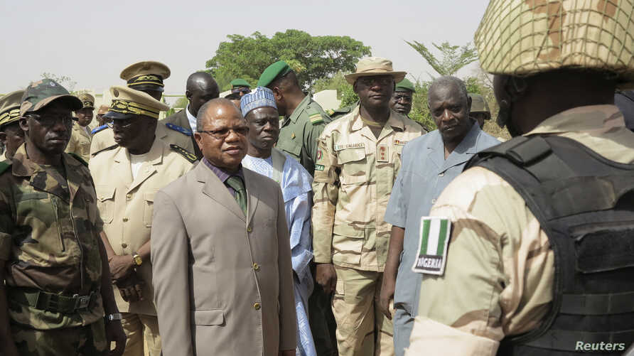 Mali's Prime Minister  Diango Cissoko (3rd L) reviews Nigerian soldiers at their base in the town of Banamba,150km (93 miles) from Bamako April 9, 2013. Cissoko paid a visit to the Nigerian Army troops base on Tuesday, reported local media.
