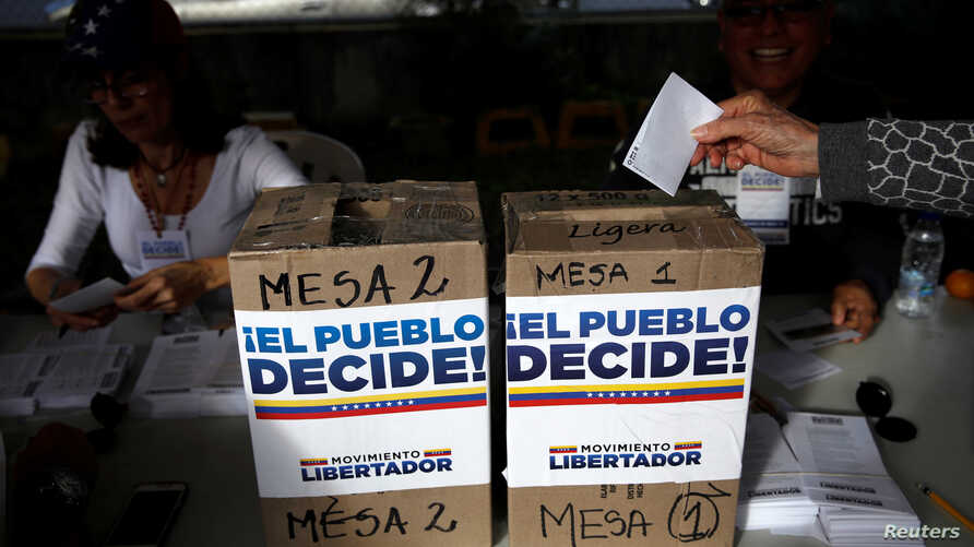 A woman casts her vote during an unofficial plebiscite against Venezuela's President Nicolas Maduro's government and his plan to rewrite the constitution, in Caracas, Venezuela, July 16, 2017.