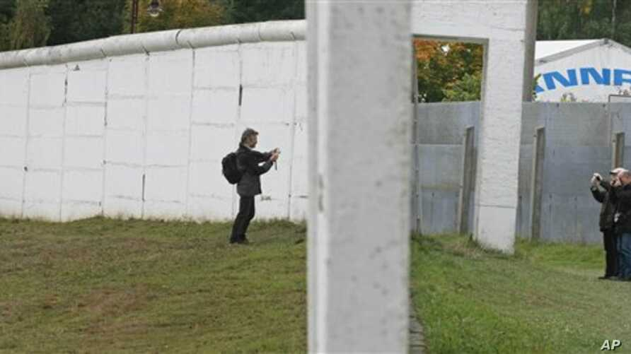 Visitors take photos from both sides of the former East/West German border wall in Moedlareuth, Germany, 3 Oct 2008 (file photo)