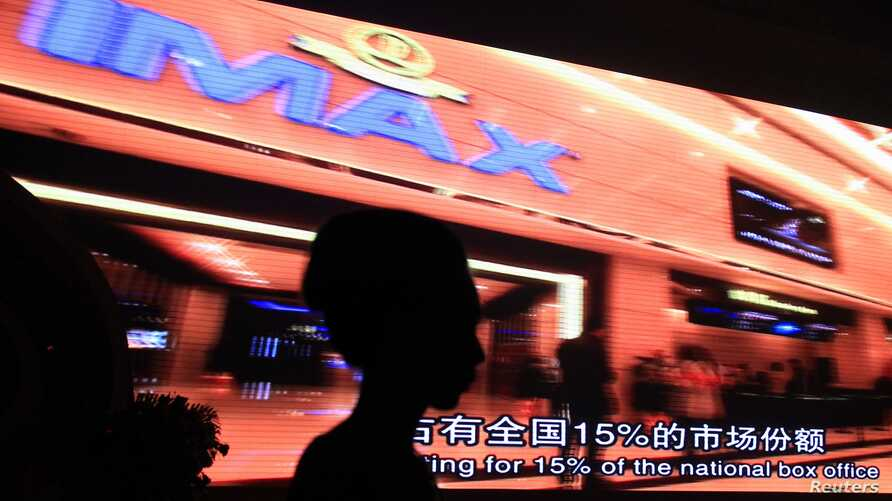Model stands in front of video presentation of deal between Chinese Wanda Group and AMC Entertainment, the world's largest operator of IMAX screens, Beijing, May 21, 2012.