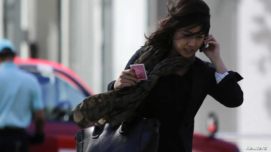 A strong wind caused by tropical storm Vongfong blows a woman's hair across her face on a street in Tokyo, October 14, 2014.
