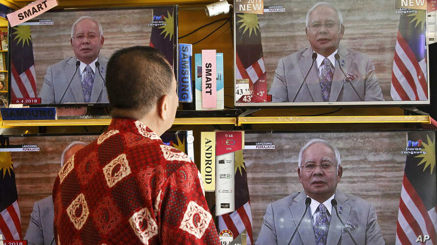 A customer watches a live broadcast of an announcement by Malaysian Prime Minister Najib Razak in Kuala Lumpur, Malaysia, April 6, 2018. Malaysia's Prime Minister Najib Razak says he will dissolve Parliament, paving the way for general elections expe