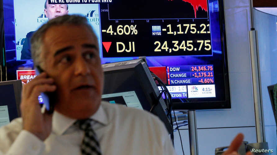 A trader works on the floor following the closing bell as a screen shows the Dow Jones Industrial Average on the New York Stock Exchange, (NYSE) in New York, Feb. 5, 2018.