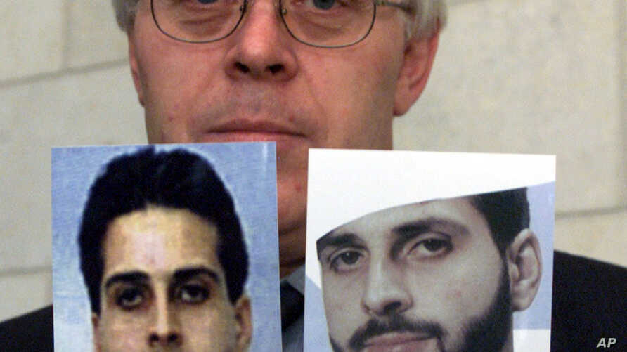 FILE - An employee of the German Federal Police holds up two handouts photos depicting Said Bahaji, also known as Zuhair al-Maghribi, with and without beard, during a press briefing in Karlsruhe, Germany, Sept. 21, 2001.