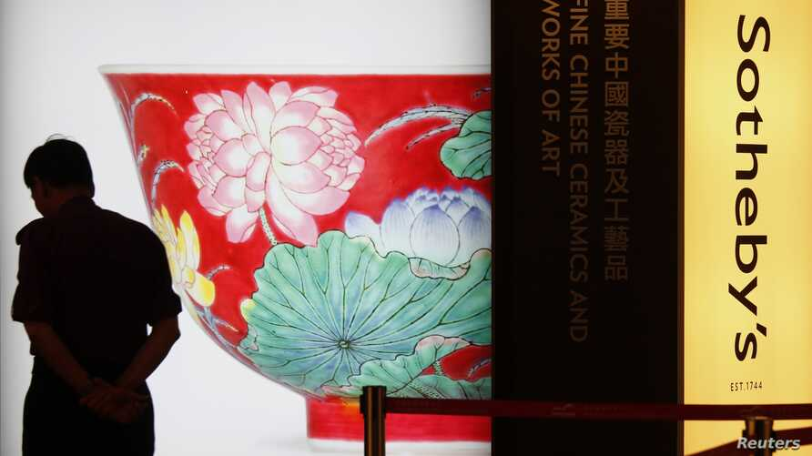 """A security guard walks past a poster of a ruby-ground falangcai """"Double-Lotus"""" bowl from China's Kangxi period, during Sotheby's preview in Hong Kong, April 2, 2013."""