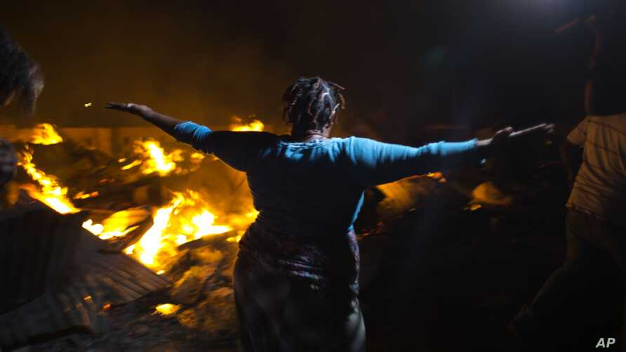 A Haitian merchant reacts as she watches flames engulf her belongings at a market Petion-Ville suburb of Port-au-Prince, Haiti, Nov. 20, 2016.