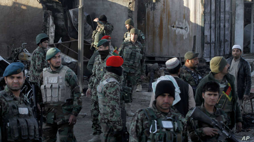 Afghan security forces inspect damages after clashes between Taliban fighters and Afghan forces in Kandahar, Afghanistan, Dec. 9, 2015.