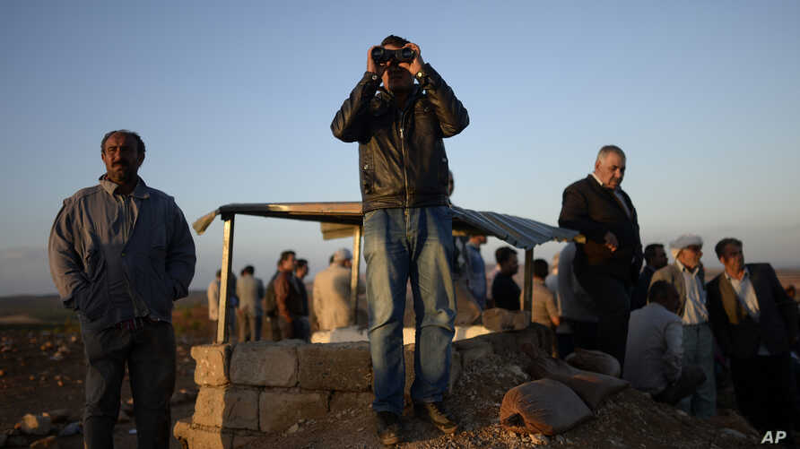 Turkish Kurds watch clashes between Syrian Kurdish fighters and Islamic State militants close to the Turkey-Syria border near Suruc, Turkey, Sept. 28, 2014.