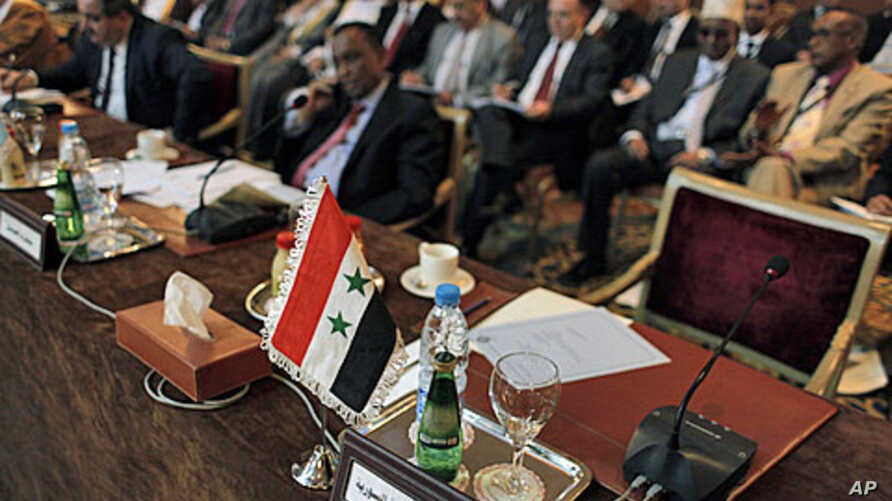 """The Syrian flag and a sign in Arabic that reads, """"the Syrian Arabic Republic,"""" is seen in front of the empty chair of the Syrian representative during the Arab League Syria Group and foreign ministers meeting in Cairo, Egypt Sunday, February 12, 2012"""