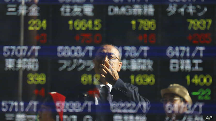 FILE - a man is reflected on an electronic stock indicator of a securities firm in Tokyo. From Australia to Zambia, Chile to Indonesia, the pain of China's sharp economic slowdown is being felt in the form of depressed commodity prices, elevated unem