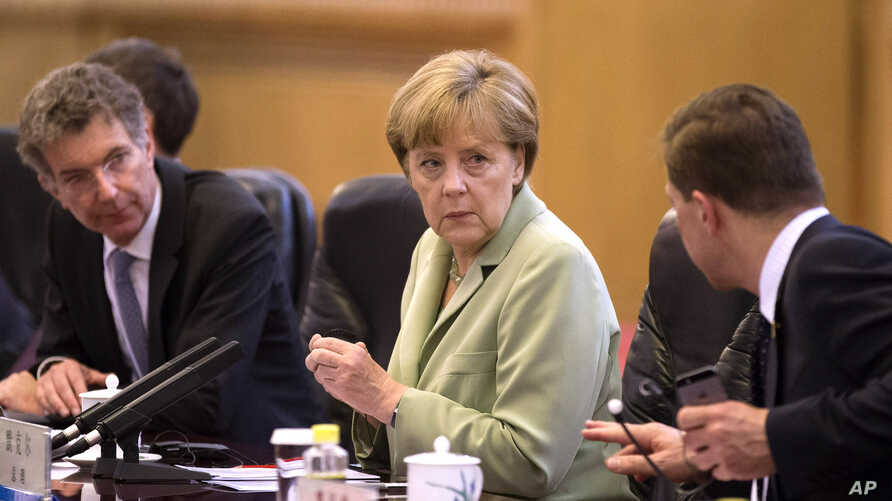 German Chancellor Angela Merkel, center, chats with her delegates as she attends a bilateral meeting with Chinese Premier Li Keqiang at the Great Hall of the People in Beijing, China, July 7, 2014.