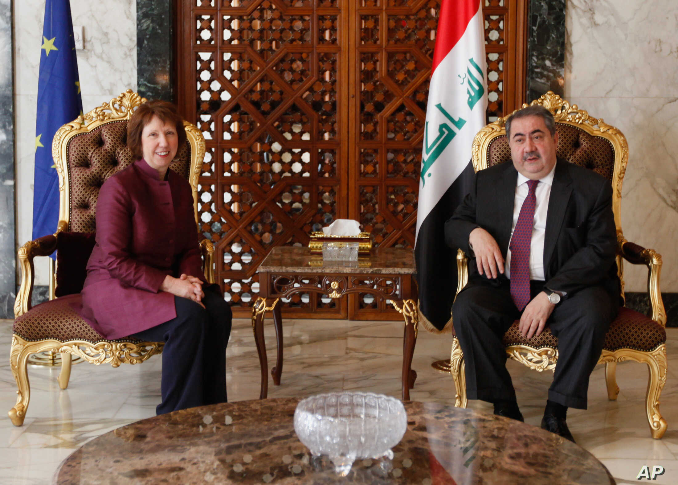 Iraq's Foreign Minister Hoshyar Zebari, right, meets with EU foreign policy chief Catherine Ashton upon her arrival at Baghdad International Airport in Iraq, May 23, 2012.