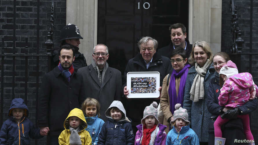 Labour peer Alf Dubs (C) poses with protestors as he delivers a petition to Number 10 Downing Street opposing the closure of a government scheme to bring unaccompanied child refugees to Britain from Europe, in London, Feb. 11, 2017.