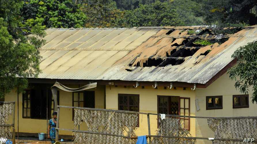 FILE - A woman stands outside the damaged roof of a school's dormitory, after it was set on fire, in Bafut, in the northwest English-speaking region of Cameroon, Nov. 15, 2017.